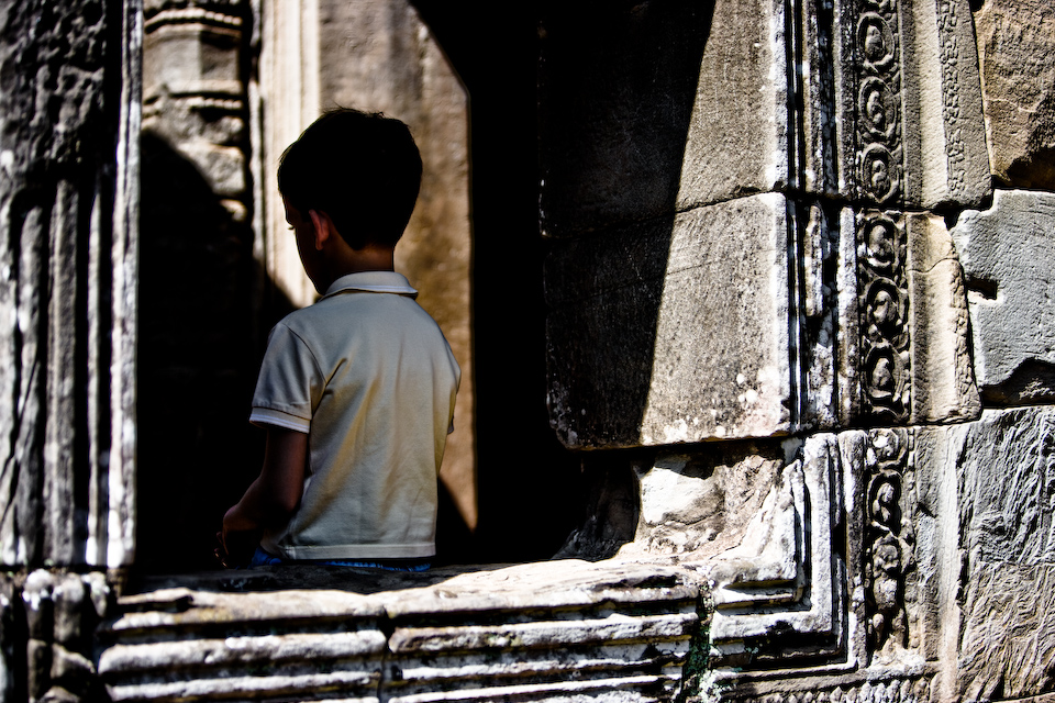 Europian kid sat on a window frame of Bayon.